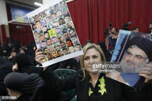 A picture taken on November 10 shows a Lebanese woman carrying portraits of Hezbollah fighters who died in combat in Syria and a portrait of Hassan...