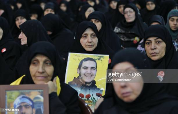 A picture taken on November 10 shows relatives of Hezbollah fighters who died in combat in Syria carrying the portraits of their relatives during a...