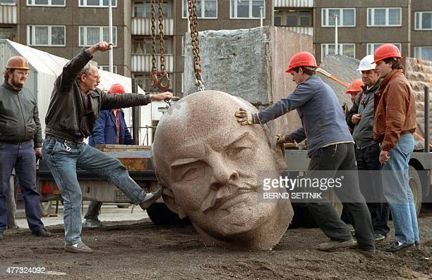 Picture taken on November 13 1991 in Berlin shows workers standing next to the head of a statue being dismantled of Russian communist revolutionary...