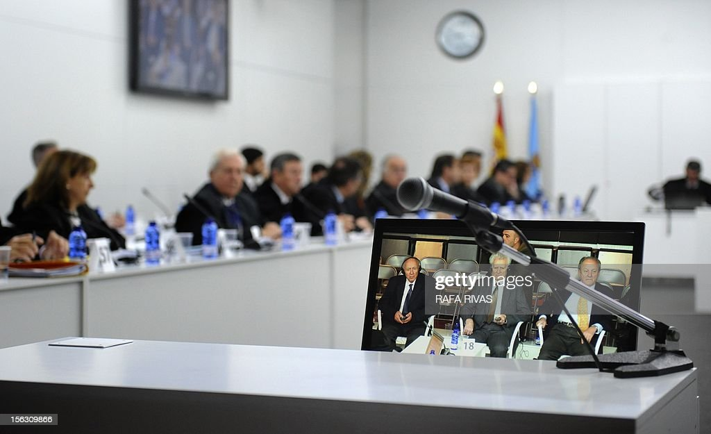 A picture taken on November 13, 2012 shows a screen with Jose Luis Lopez-Sors (R), former head of the Spanish merchant navy, Greek chief engineer Nikolaos Argyropoulos (C) and Apostolos Mangouras (L), Greek captain of the petrol tanker Prestige, attending the third day of their trial over the sinking of the Prestige, the worst oil spill in spain's history, in Coruna. Ten years after the sinking of the Prestige oil tanker off Spain, the ship's Greek captain and three others went on trial over the worst oil spill in the country's history.