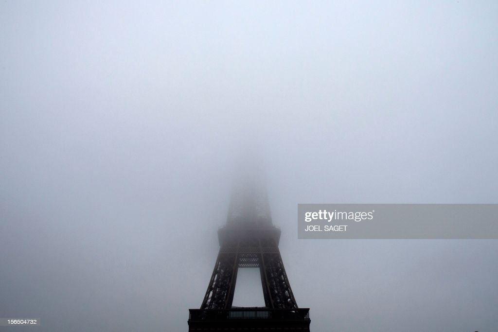 A picture taken on November 15, 2012 in Paris shows the eiffel tower partly hidden in the fog. AFP PHOTO /JOEL SAGET