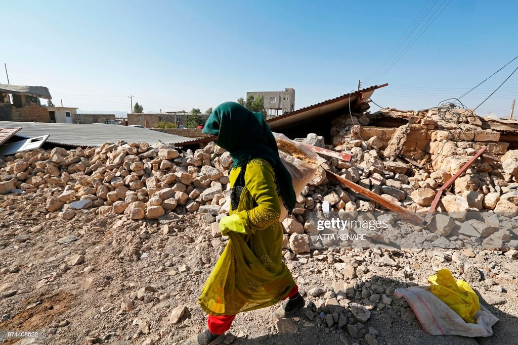 TOPSHOT - A picture taken on November 15, 2017 shows an Iranian woman walking past the rubble of a building in Kouik village near to Sarpol-e Zahab, two days after a 7.3-magnitude earthquake struck Iran's western Kermanshah province near the border with Iraq, leaving hundreds killed and thousands homeless. Iranian authorities scramble to help tens of thousands of people left homeless by a major quake on the border with Iraq that killed more than 400 people as anger mounts among residents at what they see as a slow response. /
