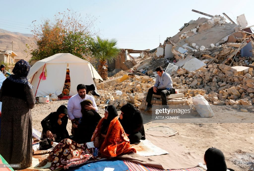 TOPSHOT - A picture taken on November 15, 2017 shows Iranians sitting next to the rubble of their homes two days after a 7.3-magnitude earthquake struck the Kouik village near to Sarpol-e Zahab in Iran's western Kermanshah province near the border with Iraq, leaving hundreds killed and thousands homeless. Iranian authorities scramble to help tens of thousands of people left homeless by a major quake on the border with Iraq that killed more than 400 people as anger mounts among residents at what they see as a slow response. /