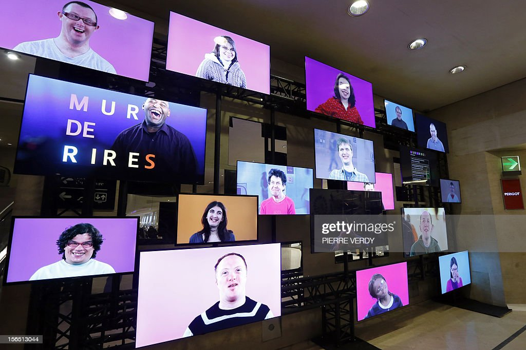 A picture taken on November 16, 2012 shows screens displayed as part of the installation entitled 'Wall of Laughs' by French film maker Nicolas Favreau at the Louvre Carrousel in Paris. The event, featuring on TV disabled people laughing, takes place until November 20, 2012 during the Extra-Ordinary Month festival.