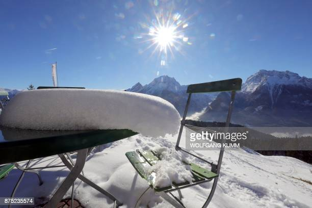 A picture taken on November 16 2017 in Berchtesgaden in the southern German state of Bavaria shows a table and a chair covered with snow as the sun...