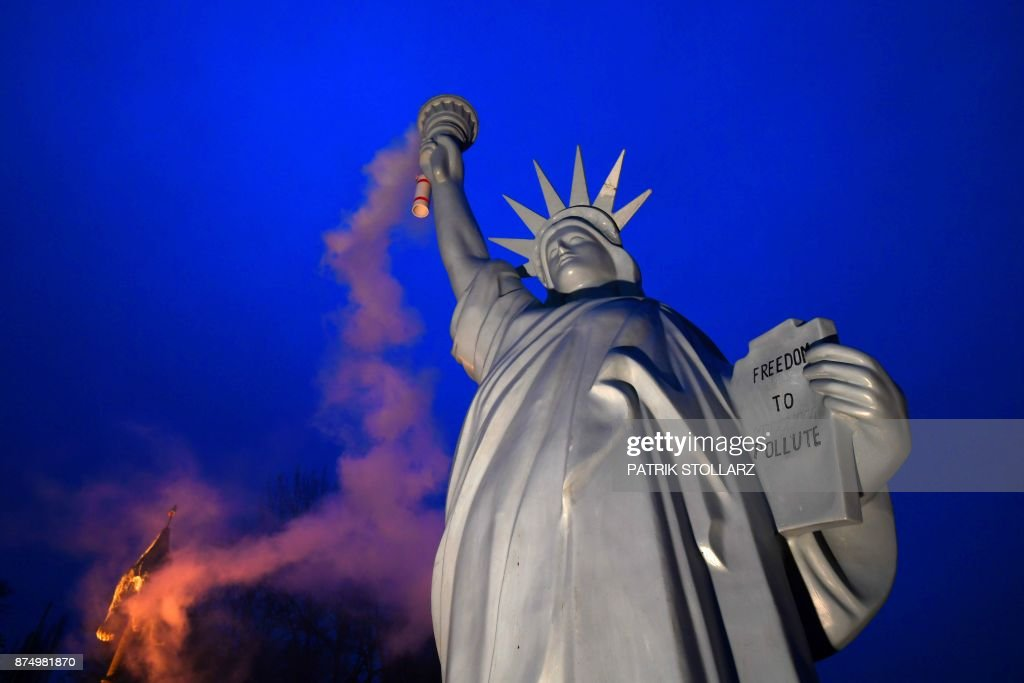 TOPSHOT - A picture taken on November 16, 2017 shows a replica of the Statue of Liberty emitting smoke from the torch created by Danish artist Jens Galschiot and displayed at the Rheinaue park during the COP23 United Nations Climate Change Conference in Bonn, Germany. /