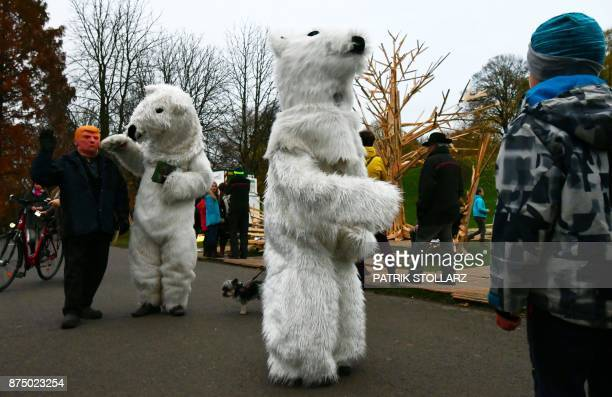 A picture taken on November 16 2017 shows people dressed up in polar bear costumes and a man with a mask of US president Donald Trump during a...