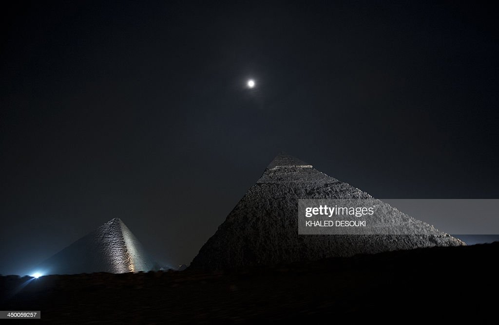 A picture taken on November 16, 2013, shows the moon above the pyramids in Giza, on the outskirts of Cairo.