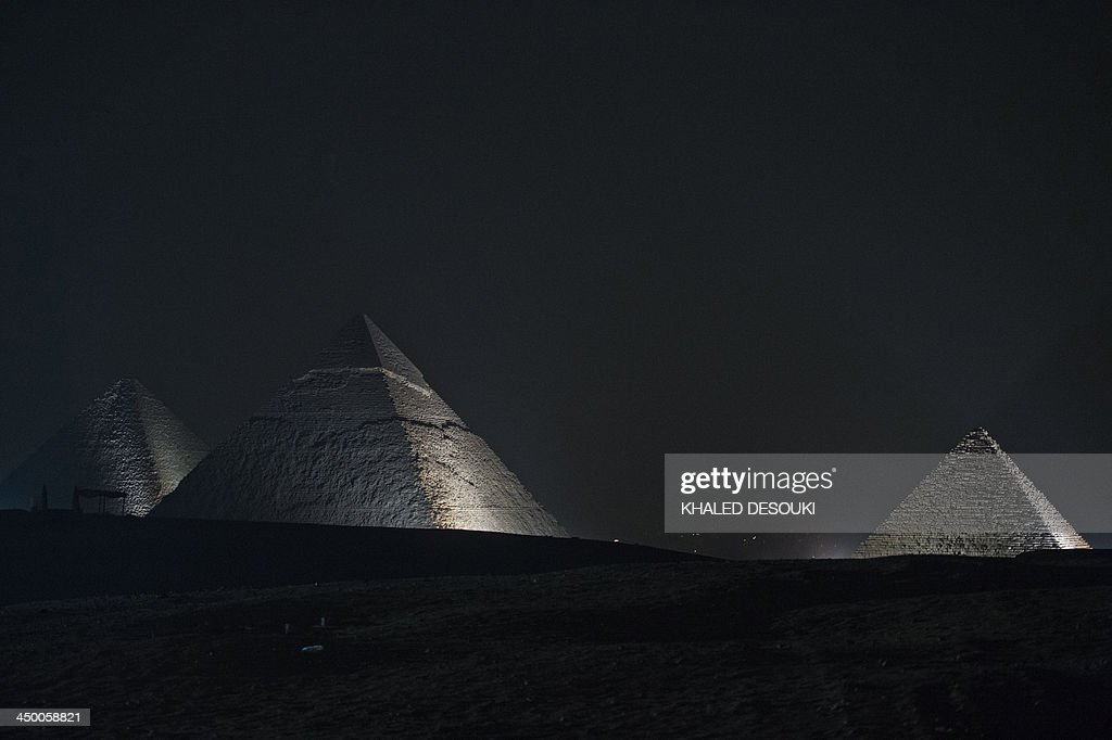 A picture taken on November 16, 2013, shows the pyramids lit up at night in Giza, on the outskirts of Cairo.