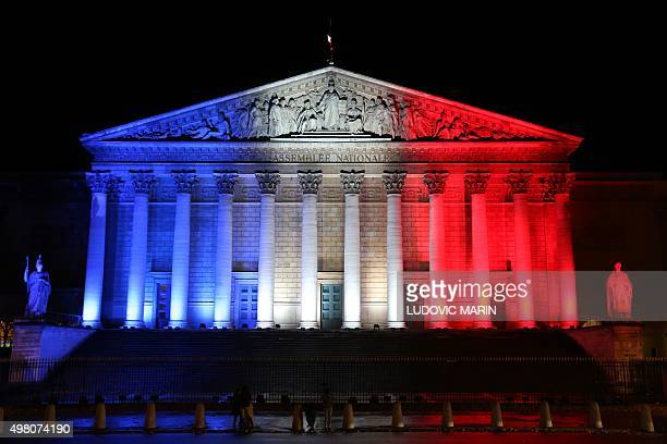 A picture taken on November 17 2015 in Paris shows the Palais Bourbon French national assembly illuminated with the colours of the French flag in...
