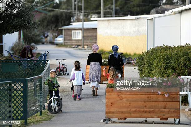 A picture taken on November 17 2016 shows families in a street of the settlement outpost of Amona which was established in 1997 in the...