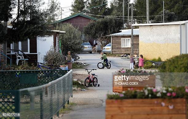 A picture taken on November 17 2016 shows kids playing in a street of the settlement outpost of Amona which was established in 1997 in the...