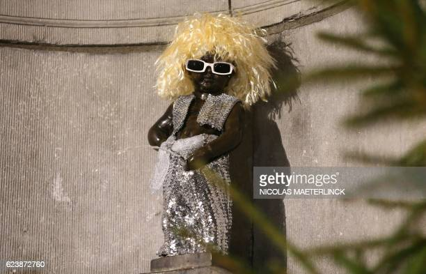 A picture taken on November 17 2016 shows the small bronze sculpture of Manneken Pis dressed as French singer Michel Polnareff in Brussels / AFP /...