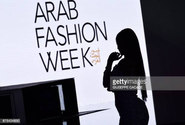 A picture taken on November 17 2017 shows the silhouette of a woman seen during Arab Fashion Week in Dubai / AFP PHOTO / GIUSEPPE CACACE