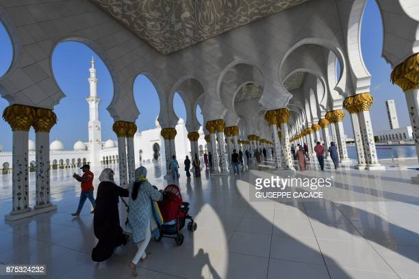 A picture taken on November 17 2017 shows visitors walking in the courtyard of the Sheikh Zayed Grand Mosque in the UAE capital Abu Dhabi / AFP PHOTO...