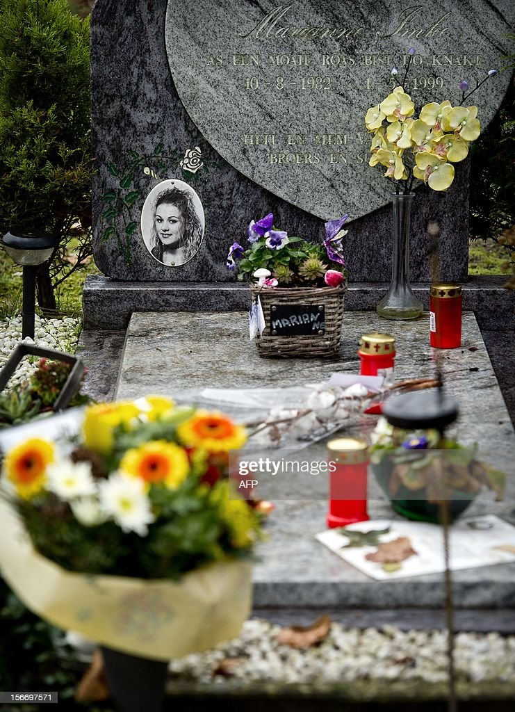 Picture taken on November 19, 2012 shows flowers and candles set up on the grave of Marianne Vaatstra in Zwaagwesteinde, as the police announced they have arrested a Dutch man in connection with the 1999 murder of 16-year-old Marianne Vaatstra. The police traced the man after asking some 8,000 men to give dna samples in the hope of finding a link to the killer. AFP PHOTO /ANP / Koen van Weel netherlands out