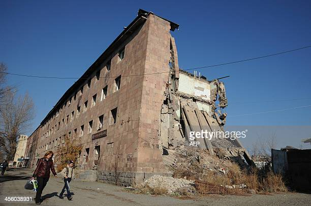 A picture taken on November 19 shows a woman with child walking past a building left half destroyed by the 1998 devastating earthquake in Gyumri the...