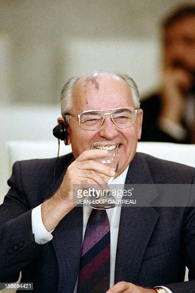 A picture taken on November 20 1990 shows Soviet President Mikhail Gorbachev smiling while enjoying a drink during a working session in Paris on the...