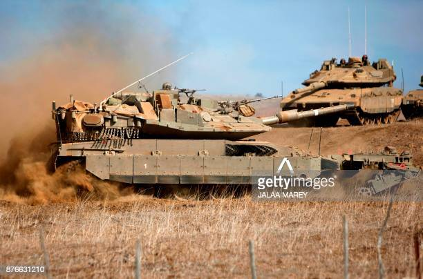 A picture taken on November 20 2017 shows a Merkava MkIV tank strapped with antimine rollers taking part in a military exercise near the border with...