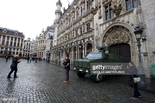 A picture taken on November 21 2015 shows people posing for pictures in front of a military armoured vehicle next to the Grande Place square in...