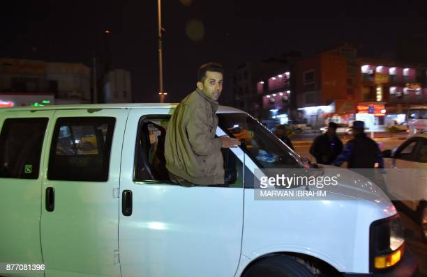 A picture taken on November 21 2017 shows a man riding out of the window of a car transporting one of the victims of a suicide car bomb attack in the...
