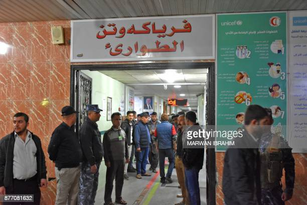 A picture taken on November 21 2017 shows Iraqis and members of the security forces waiting in the hallway of a hospital in the northern Iraqi town...