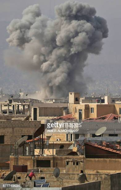 TOPSHOT A picture taken on November 23 2017 shows people standing on rooftops as they watch smoke rise following a reported air strike on the...