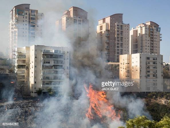 A picture taken on November 24 2016 shows a fire raging in the northern Israeli port city of Haifa Hundreds of Israelis fled their homes on the...