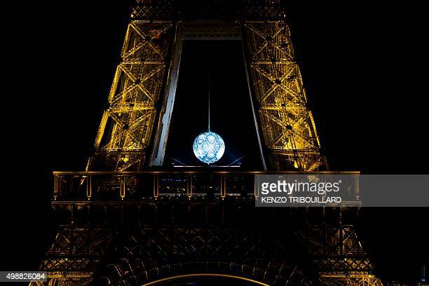 A picture taken on November 26 2015 shows the 'Earth Crisis' globe by US artist Shepard Fairey hanging from the Eiffel Tower in Paris on November 26...