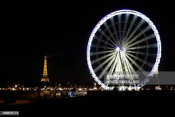 A picture taken on November 26 2015 shows the Eiffel Tower and the Ferris wheel on Place de la Concorde in Paris / AFP / KENZO TRIBOUILLARD