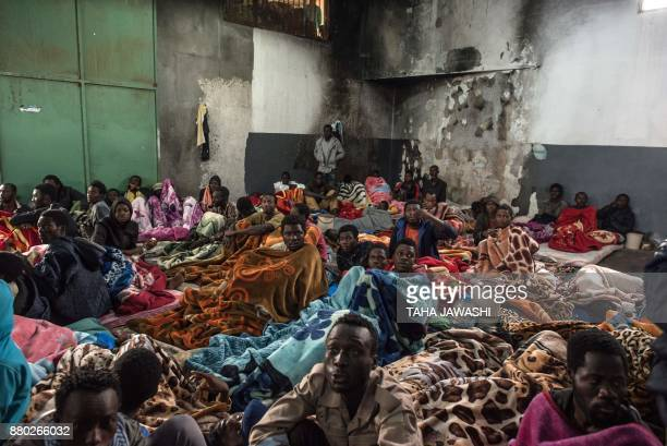 A picture taken on November 27 2017 shows African migrants sitting in a packed room with their beds and blankets at the Tariq AlMatar detention...