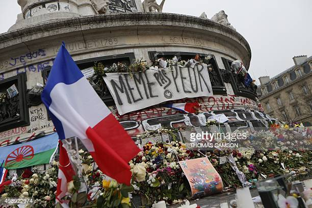 A picture taken on November 27 shows French national flags candles and flowers at a makeshift memorial in Place de la Republique square in Paris for...