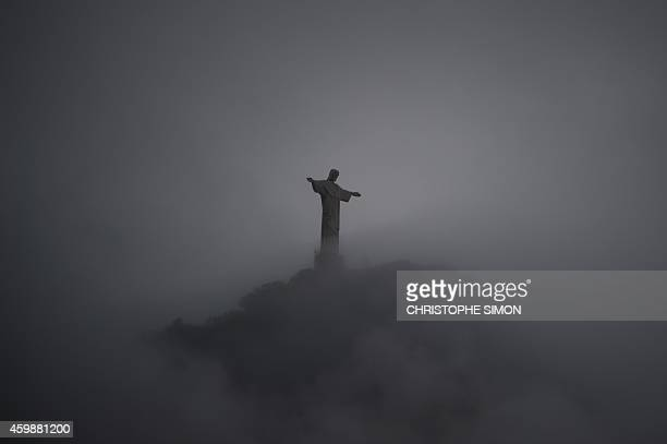 Picture taken on November 30 2014 of the Christ the Reedemer statue surrounded by clouds atop the Corcovado mountain seen from Copacabana in Rio de...
