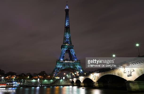 A picture taken on November 30 2015 shows the Eiffel Tower lit up with green color and messages to prevent global warming during the first day of the...