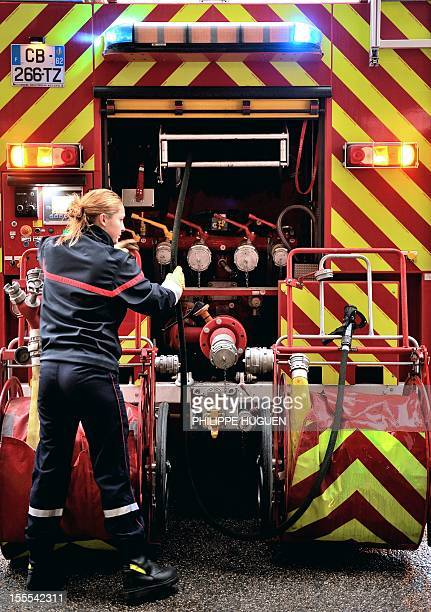 A picture taken on November 4 2012 shows a firefighter woman checking a fire hose at the rear of a truck in a firehouse in BoulognesurMer in northern...
