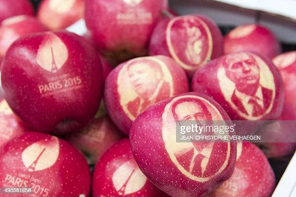 A picture taken on November 4 2015 shows an apple marked with the portraits of French President Francois Hollande French Foreign Minister Laurent...