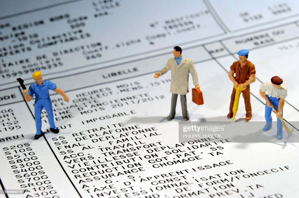 A picture taken on November 6, 2012 in Lille shows figurines representing employees put on a pay slip displaying details of the payroll tax.
