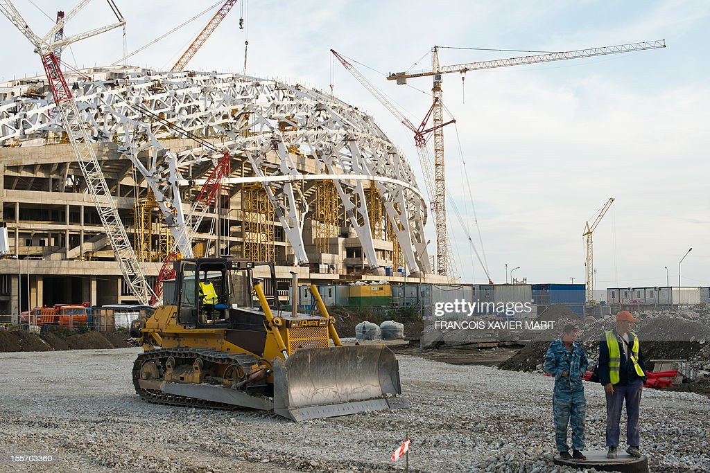 A picture taken on November 6, 2012 shows workmen standing by the fisht olympic stadium which will host the opening and closing ceremonies at the upcoming 2014 winter olympics in Sochi. MARIT