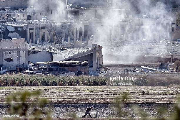 A picture taken on November 6 2014 from the Turkish city of Mursitpinar shows a People's Protection Units fighter runing for cover during a shelling...