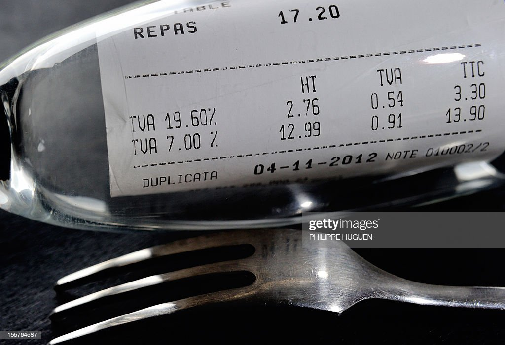 A picture taken on November 8, 2012 in a restaurant in Lille shows a bill, rolled up in a glass set up next to a fork, with the 19,60 percent value added tax (VAT), and the 7 percent VAT rate. The government announced on November 6, 2012 plans to increase VAT from 19,60% to 20% which is applied to alcoholic drinks sold in bars, cafes and restaurants. The move to increase the rate of value added tax (VAT) charged on restaurant food and hotel accommodation from seven to 10 percent was dubbed 'brutal' by the trade with representative bodies warning it will cost tens of thousands of jobs.