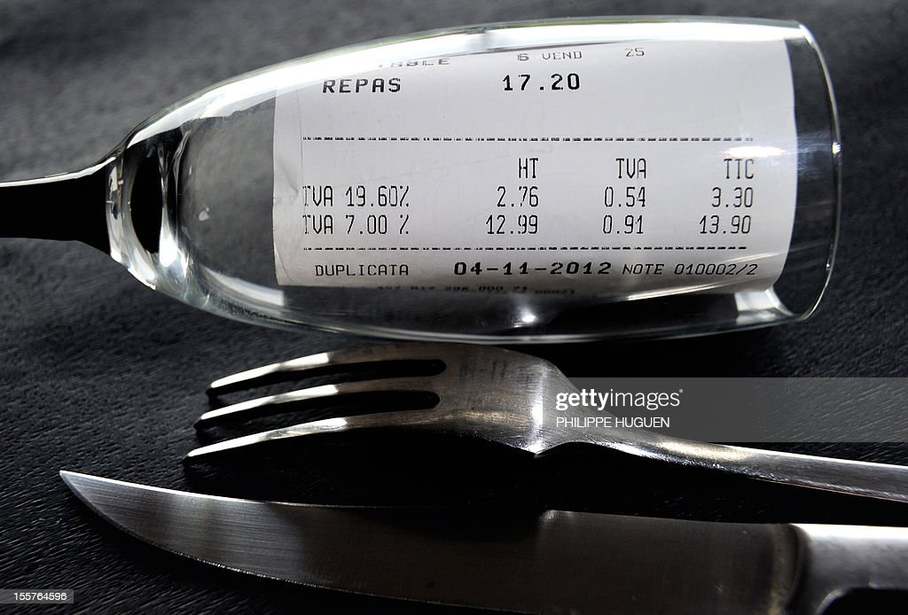 A picture taken on November 8, 2012 in a restaurant in Lille shows a bill, rolled up in a glass set up next to a fork and a knife, with the 19,60 percent value added tax (VAT), and the 7 percent VAT rate. The government announced on November 6, 2012 plans to increase VAT from 19,60% to 20% which is applied to alcoholic drinks sold in bars, cafes and restaurants. The move to increase the rate of value added tax (VAT) charged on restaurant food and hotel accommodation from seven to 10 percent was dubbed 'brutal' by the trade with representative bodies warning it will cost tens of thousands of jobs.