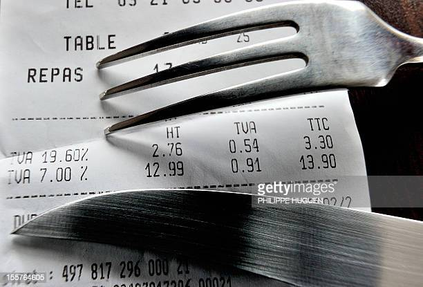 A picture taken on November 8 2012 in a restaurant in Lille shows a fork and knife set up on a bill with the 1960 percent value added tax and the 7...