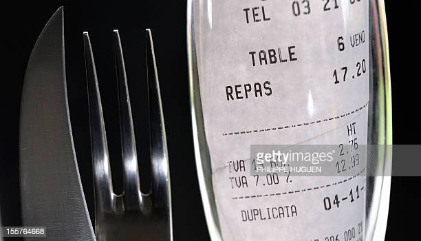 A picture taken on November 8 2012 in a restaurant in Lille shows a bill rolled up in a glass set up next to a fork and a knife with the 1960 percent...