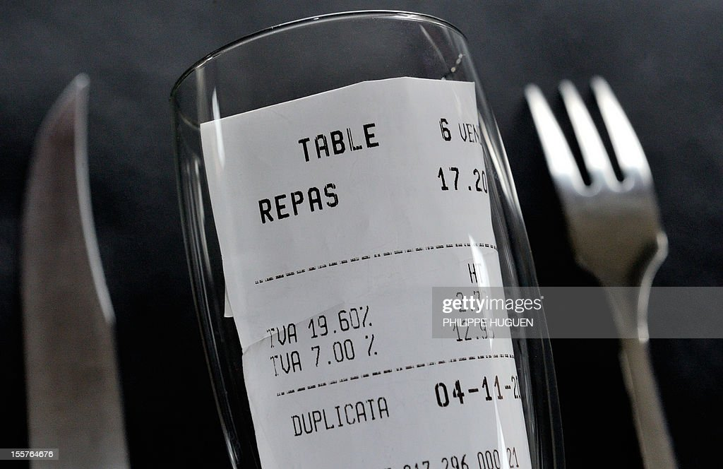 A picture taken on November 8, 2012 in a restaurant in Lille shows a bill, rolled up in a glass set up between a fork and a knife, with the 19,60 percent value added tax (VAT), and the 7 percent VAT rate. The government announced on November 6, 2012 plans to increase VAT from 19,60% to 20% which is applied to alcoholic drinks sold in bars, cafes and restaurants. The move to increase the rate of value added tax (VAT) charged on restaurant food and hotel accommodation from seven to 10 percent was dubbed 'brutal' by the trade with representative bodies warning it will cost tens of thousands of jobs.