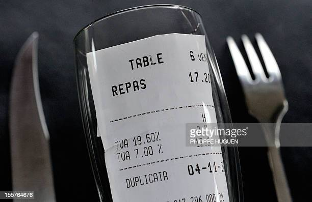 A picture taken on November 8 2012 in a restaurant in Lille shows a bill rolled up in a glass set up between a fork and a knife with the 1960 percent...