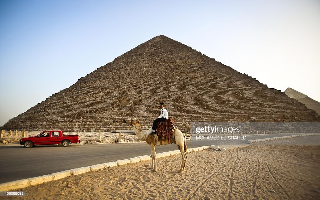A picture taken on November 9 shows a police officer riding a camel past the pyramids of Menkaure and Khafre in Giza on the outskirts of Cairo The...