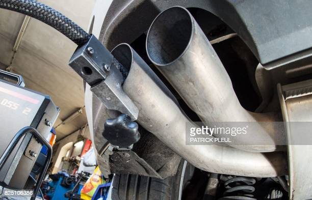 Picture taken on October 1 2015 shows a hose sticking in the exhaust pipe of a Volkswagen diesel car during an emission test at a workshop in...