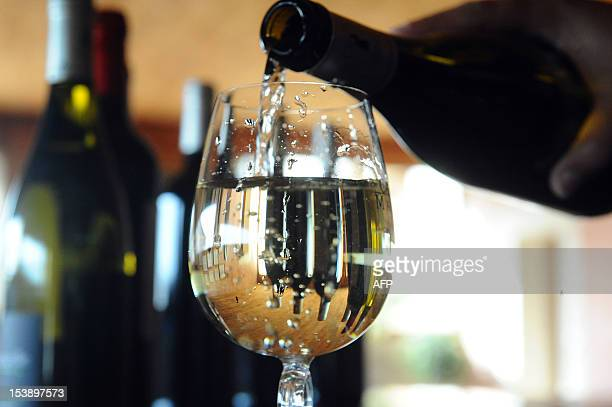 A picture taken on October 10 2012 shows French wine owner and producer Caroline Cassot pouring white wine in a glass in Prayssac in the French...