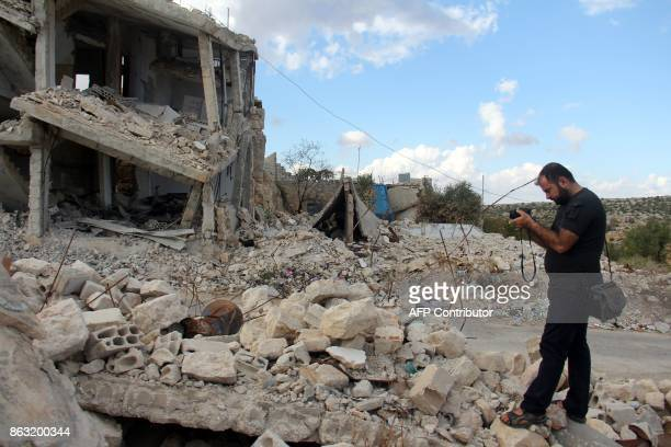 A picture taken on October 10 shows Syrian photographer Ahmed Khatib taking a picture of a damaged building in the village of Marayan in the Idlib...