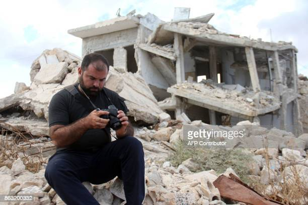 A picture taken on October 10 shows Syrian photographer Ahmed Khatib checking his pictures next to damaged building in the village of Marayan in the...